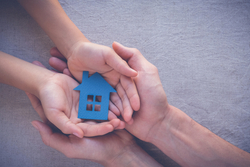 Child and parent's hands holding a model house