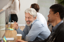 An older man helps his younger colleague while laughing together
