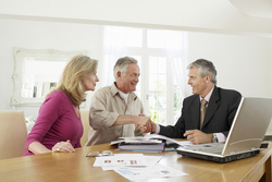 an older couple shake hands with their financial planner
